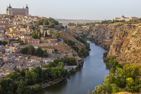 Old town cityscape with Alcazar and river Tagus at sunset, Toledo, Spain