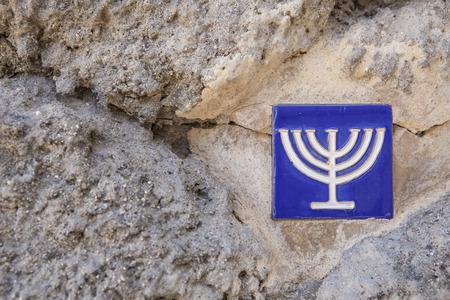 sephardic: Glazed tile over stone wall with menorah symbol marking the ancient jewish quarter, Toledo, Spain