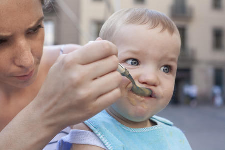 smeared baby: Mother feeding her baby boy with fruit mush outdoors Stock Photo