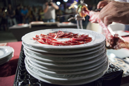 slicer: Master slicer cutting iberian cured ham at public exhibition. Selective focus point