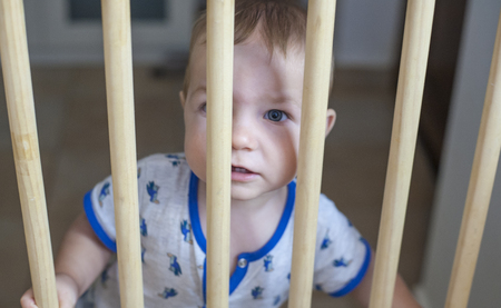 he old: One year old baby boy behind the wooden safety gate of stairs. He is trying to go upstairs