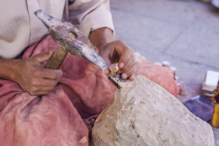 craftwork: Artisan makes pieces for mosaic craftwork. He is shaping pieces from glazed tiles Stock Photo