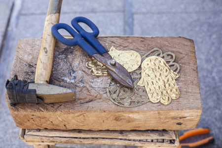 Craftsman bench with tools for engrave hamsa palm-shaped brass amulets