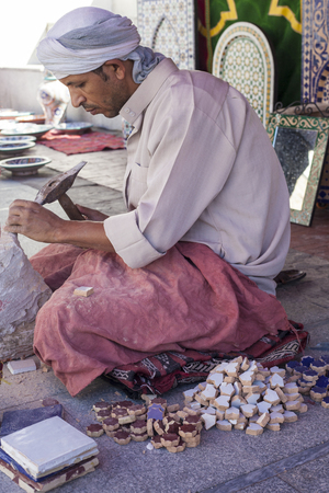 craftwork: Badajoz, Spain - September 24, 2016: Makes Artisan craftwork pieces for mosaic. I is shaping pieces from glazed tiles Editorial