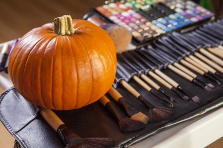 Set of brushes for makeup in a black cover with pumpkin. Halloween making up objects Stock Photo