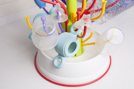 nasal: Baby drainer full of plastic tableware objects as baby bottles, nasal aspirator, milk bowls, teats and others