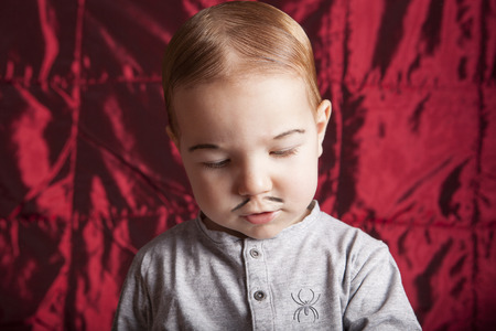 adams: Portrait of a little boy dressed-up for halloween party. Red satin background
