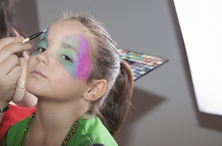 Little cute girl making facepaint before halloween party. The make-up artist is applying some colors while she is looking to the camera