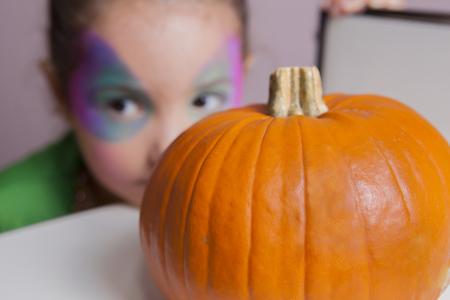 Little cute girl behind pumpkin after making facepaint for halloween party