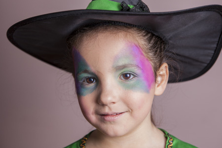 costumed: Little cute girl made up and costumed as a witch before halloween party. She is smiling