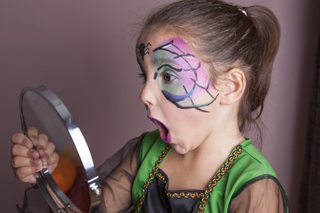 maquillaje infantil: Niña sorprendida mirando en el espejo después de la sesión de pintura de la cara antes de la fiesta de Halloween