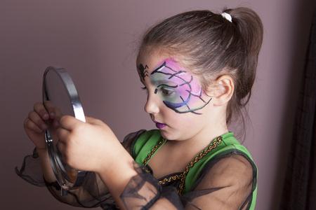 maquillaje infantil: Niña que mira en el espejo después de la sesión pintura de la cara antes de la fiesta de Halloween