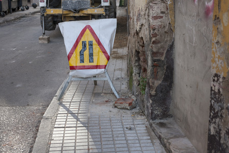 obedecer: Traffic sign outdoors. Road sign lane narrowing. In the background, blurred a roadworks machine