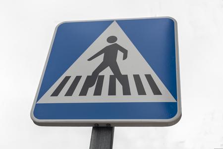 obedecer: Paso de peatones poste de señales de tráfico. Aislado sobre el cielo gris Foto de archivo