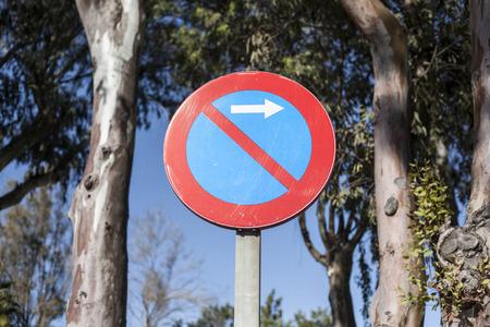 obey: Ningún polo aparcamiento señal de tráfico con la flecha blanca con los árboles del parque como un fondo
