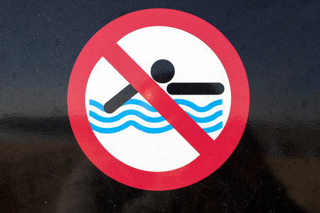 no swimming sign: No Swimming sign over black background Stock Photo