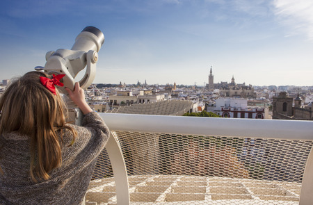 metropol parasol: Little girl with telescope pointing to old town landmarks over Metropol Parasol roof, Seville, Spain