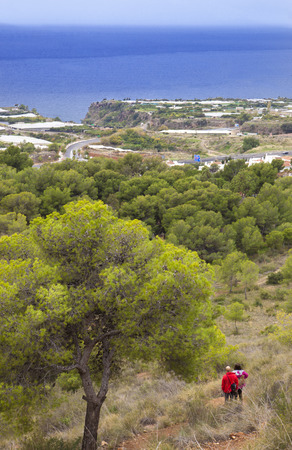 nerja: Couple hiking by path over Nerja Caves. Overlooking Town of Nerja, Malaga, Spain