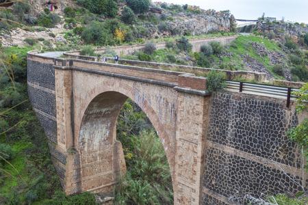 nerja: Couple hiking by Old national highway bridge, Nerja, Malaga, Spain Stock Photo