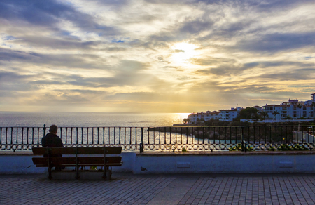 Man observing a magnificent sunrise at the Balcon de Europa in Nerja, Spain