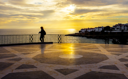 Mature female photographer walking at Balcon de Europa and looking the magnificent sunrise, Nerja, Spain