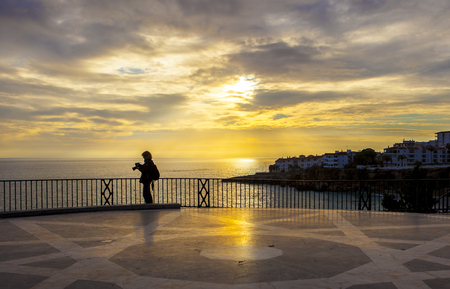 Mature female photographer checking pictures at Balcon de Europa and looking the magnificent sunrise, Nerja, Spain