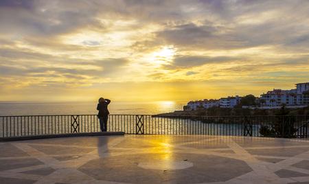 Fotógrafo de sexo femenino maduro que toma imágenes a Balcón de Europa y mirando la salida del sol magnífica, Nerja, España Foto de archivo - 70413176