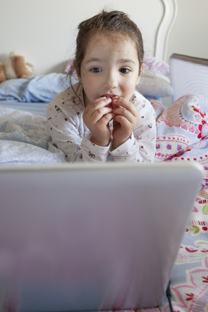 Little girl lying in bed and playing with a laptop in his bedroom. She looks intrigued