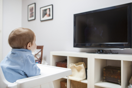 side viewing: Baby boy watching TV. He is sitting on his highchair Stock Photo