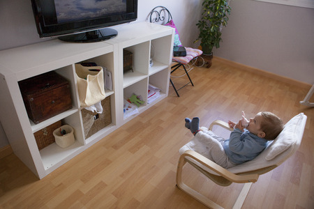 watching television: Baby boy watching television. He is sitting on his childrens armchair Stock Photo