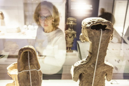 Madrid, Spain - February 24, 2017: Elder woman observing Carthaginian goddess figurines, at National Archeological  Museum of Madrid