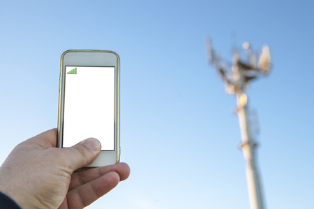 Man holds mobile phone on hand pointing to telephony antenna or base station Stock Photo