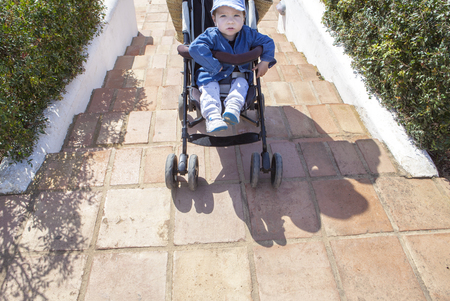 perambulator: Mother carries a stroller down the stairs in garden without ramp for the disabled and baby prams