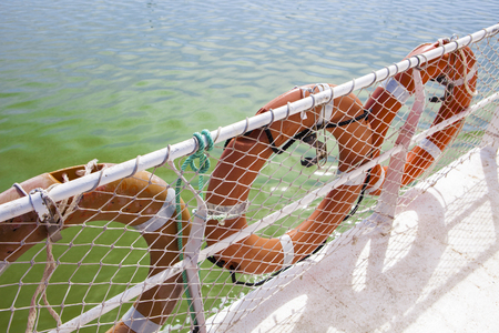 Three lifebuoy on ferry board with green river waters at bottom, Huelva, Spain