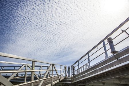 floccus: Marina footbridge with cloud formations in the sky called Altocumulus floccus, El Rompido Cartaya, Huelva, Spain