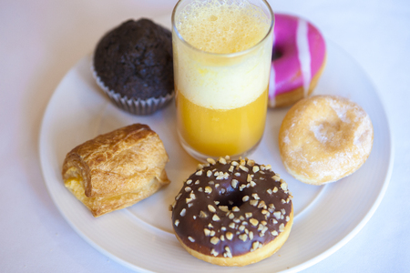 Plate full of pastries with orange juice glass. High angle view