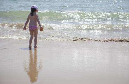 Meisje speelt en spat op strand strand. El Rompido, Huelva, Spanje Stockfoto - 76627382