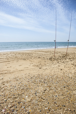 floccus: Two fishing rods hammered on the beach sand. He is launching the line. Sea angling sport at the beach, Huelva, Spain