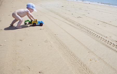 Baby boy pushing his beach toys over the sand. El Rompido, Cartaya, Huelva, Spain Stock Photo