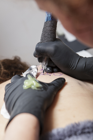 Tattoo artist applies tattoo to shoulder blade of a woman. She is outlining the tattoo