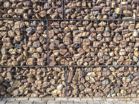 grille: Wall protected with river pebble stones in iron mesh. This structure is decorative and it has isolation features