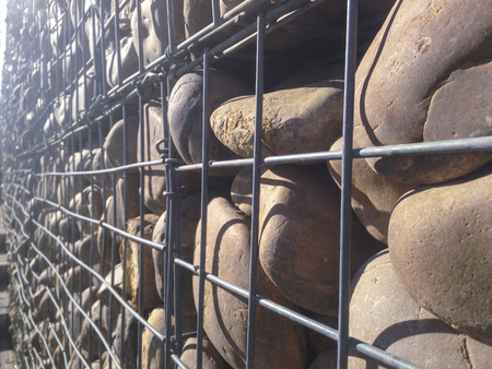 wire mesh: Wall protected with river pebble stones in iron mesh. This structure is decorative and it has isolation features