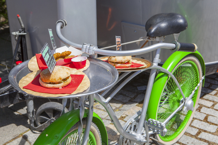 Vintage green bike used for offer meals beside food truck trailer. Sunny day  Stock Photo