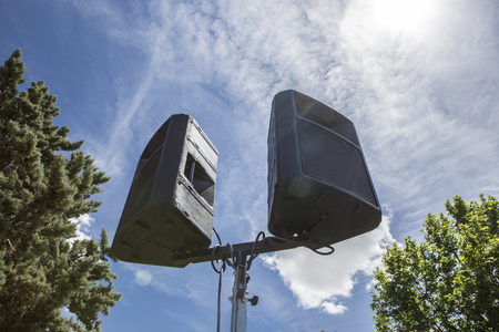 Outdoor speakers over leaf and blue cloudy sky. Low angle view
