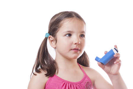 Little sick girl using medical spray for breath. Isolated over white background Stock Photo