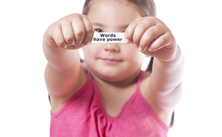Young girl holding a fortune cookie paper with the message Words have Power