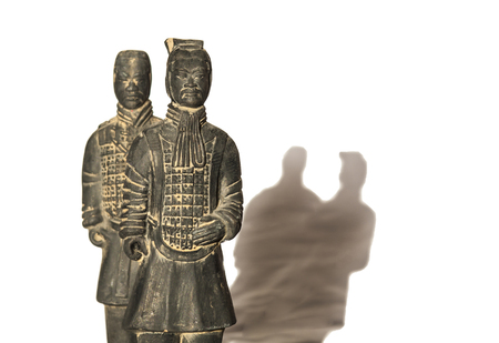 Replicas of two terracotta soldiers over white background