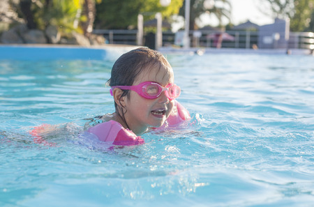 armbands: Little girl enjoying the summer at swiming pool. She wears armbands and goggles