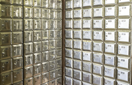 Corner full of rows of old shiny metal post office boxes Stock Photo