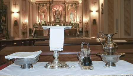 consecrated: Catholic liturgical objects displayed over table at church. Chalice, communion wafers, wine, water, ewer and basin Stock Photo